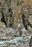 The Larja Bridge, a narrow metal swing bridge, strung with Tibetan Buddhist prayer flags, over the Dudh Koshi (or Kosi, river) below the town of Namche Bazaar, in Sagarmatha National Park, Nepal. Sagarmatha National Park was created in 1976 and honored as a UNESCO World Heritage Site in 1979.