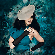 Painterly rendition of a woman with stylish hat striking a pose against a teal background with historical clock faces