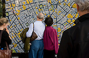 Tourists finding their way around Soho and the West End with the help of a large city map of London.