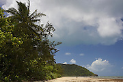 Couple look out to sea on Myall Beach by Cape Tribulation, named by Captain Cook, Queensland, Australia