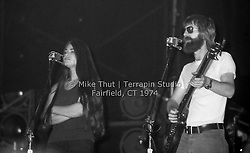Donna Jean Godchaux and Phil Lesh singing into those infamous dual cancelling mics. The Grateful Dead at Dillon Stadium in Hartford CT on 31 July 1974. Close in quarter view shot, taken at after dark with flash. Photo by Michael Thut, Fairfield CT.