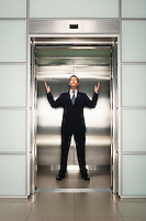 Businessman arms raised in Elevator front view