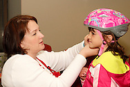 Kirsten Patterson of Dayton fits Cherie Montavon, 6 of Kettering with a new bike helmet from the Junior League of Dayton during the 10th Annual Celebrating life & health free community health fair at Sinclair's Ponitz Center in downtown Dayton, Saturday, April 21, 2012. More than 50 vendors were spread over three floors providing vision, hearing, blood pressure and other screenings, health information and entertainment.