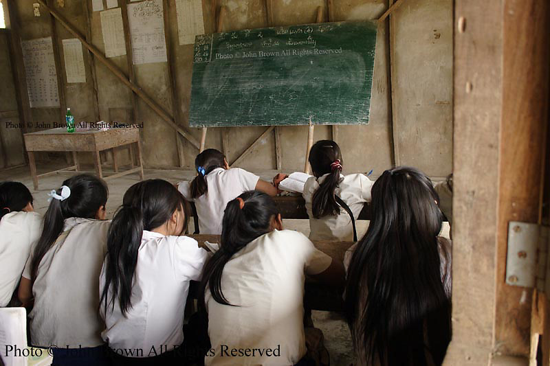 Students strive to improve their Lao language reading skills at The Ban Buamlao Primary School in Ban Buamlao, Laos. The boys sit on one side of class while the girls choose to be adjacent to open windows on this day at the rural schoolhouse.