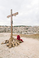"""MATERA, ITALY -6 OCTOBER 2019: A backstage scene of a Roman soldier resting by a cross during the production of """"The New Gospel"""", a film by Swiss theatre director Milo Rau, in Matera, Italy, on October 6th 2019.<br /> <br /> Theatre Director Milo Rau filmed the Passion of the Christ  under the title """"The New Gospel"""" with a cast of refugees, activists and former actors from Pasolini and Mel Gibson's films.<br /> <br /> The role of Jesus is performed by Yvan Sagnet, a Political activist born in Cameroon and who worked on a tomato farm when in 2011 he revolted against the system of exploitation and led the first farm workers' strike in southern Italy. In a series of public shoots in the European Capital of Culture Matera, Jesus will proclaimed the Word of God, was crucified (October 6th 2019) and finally rose from the dead in Rome, the capital of Catholic Christianity and seat of one of the most xenophobic governments in Europe (October 10th 2019).<br />  <br /> Parallel to the film, the humanistic message of the New Testament was transformed into the present: at the beginning of September, the campaign """"Rivolta della Dignità"""" (Revolt of Dignity), which demanded fair working and living conditions     for refugees, global freedom of travel and civil rights for all, started with a march from the southern Italian refugee camps. """"It's about putting Jesus on his feet,"""" director Milo Rau said. Led by Jesus actor Yvan Sagnet, the campaign fights for the rights of migrants who came to Europe via the Mediterranean to be enslaved by the Mafia in the tomato fields of southern Italy and to live in ghettos under inhumane conditions. The campaign and the film thus create a """"New Gospel"""" for the 21st century, a manifesto of solidarity with the poorest, a revolt for a more just and humane world."""