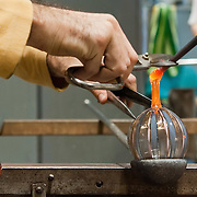 "VENICE, ITALY - DECEMBER 14:  A maestro glass maker at Eugenio Ferri & C.  in Murano makes a Christmas bauble with the ""zanfirico"" technique on December 14, 2010 in Venice, Italy. The production of glass baubles is an highly skilled process,with a variety of styles, often with the inclusion of gold and silver foil."
