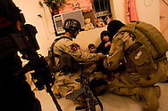 BAGHDAD, IRAQ - MAY 27: Iraqi Emergency Response Brigade (ERB) members speak with the wife of a suspected insurgent after an warrant was issued for his arrest, on May 27, 2010, on the outskirts of Baghdad, Iraq. Iraqi Special Forces and ERB and been training under US Special Forces for several years with a heavy focus on evidence collection and both legal and human rights for detained suspects. Members of the unit make little more than $700 a month and keep their identity a secret as many prevail from areas where insurgency is rife. US Special Forces are not permitted to accompany Iraqi ERB on missions unless an arrest warrant has been issued. Iraq faces multiple challenges in the lead-up to the drawn-down of US forces in Iraq, with many observers claiming that while they have the capablities of handling home-grown problems, they are far from being able to tackle external threats. Political wrangling has reportedly fostered greater instability throughout the country with fears of renewed sectarian violence breaking out as insurgents set-up attacks in an attempt to exploit vulnerabilities amongst the populace. (Photo by Warrick Page)