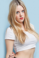 Portrait of beautiful young blond woman with red lips over light blue background