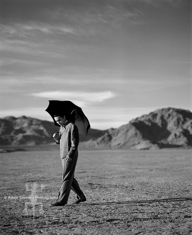 Young businessman with umbrella walking on landscape (B&W)