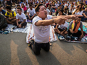 "07 MARCH 2015 - NAKHON CHAI SI, NAKHON PATHOM, THAILAND: A man crawls towards the stage channeling the power of his spiritual tattoo at the Wat Bang Phra tattoo festival. Wat Bang Phra is the best known ""Sak Yant"" tattoo temple in Thailand. It's located in Nakhon Pathom province, about 40 miles from Bangkok. The tattoos are given with hollow stainless steel needles and are thought to possess magical powers of protection. The tattoos, which are given by Buddhist monks, are popular with soldiers, policeman and gangsters, people who generally live in harm's way. The tattoo must be activated to remain powerful and the annual Wai Khru Ceremony (tattoo festival) at the temple draws thousands of devotees who come to the temple to activate or renew the tattoos. People go into trance like states and then assume the personality of their tattoo, so people with tiger tattoos assume the personality of a tiger, people with monkey tattoos take on the personality of a monkey and so on. In recent years the tattoo festival has become popular with tourists who make the trip to Nakorn Pathom province to see a side of ""exotic"" Thailand.   PHOTO BY JACK KURTZ"