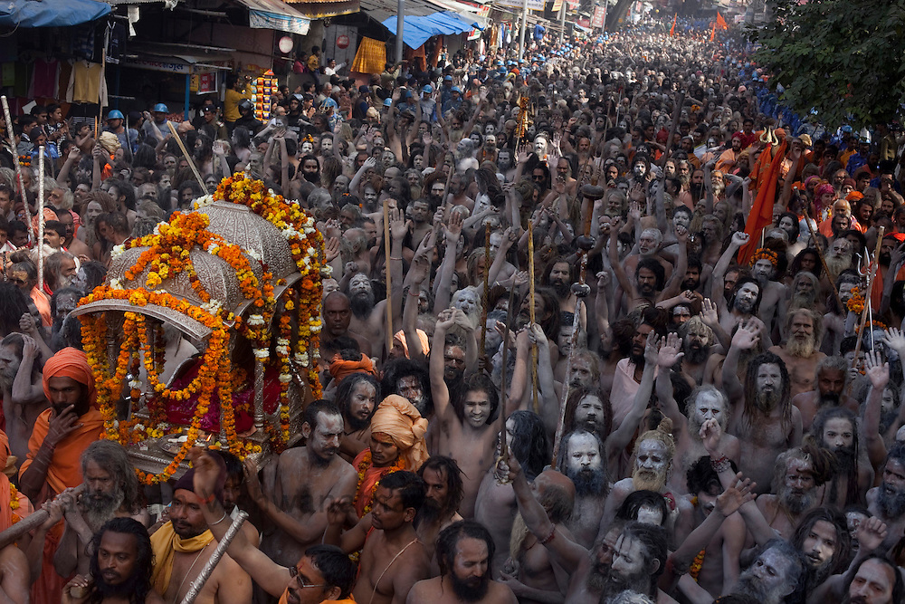 "A Naga sadhus walk past the modern streets of Haridwar during  the ""Shayi Snan"" (royal bath) at the Maha Kumbh ceremony in Haridwar, February 12, 2010.  Photographer:Prashanth Vishwanathan"
