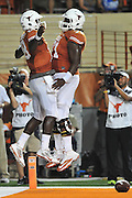 AUSTIN, TX - OCTOBER 18:  Tyrone Swoopes #18 of the Texas Longhorns celebrates after scoring a touchdown with Camrhon Hughes #71 against the Iowa State Cyclones on October 18, 2014 at Darrell K Royal-Texas Memorial Stadium in Austin, Texas.  (Photo by Cooper Neill/Getty Images) *** Local Caption *** Tyrone Swoopes; Camrhon Hughes