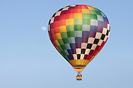 Middletown, New York - A hot air balloon flies past the moon after taking off from Randall Airport on April 12, 2014.