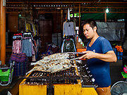 17 SEPTEMBER 2018 - BANGKOK, THAILAND:  A man sells grilled fish in Klong San market, next to the ICONSIAM development. ICONSIAM is a mixed-use development on the Thonburi side of the Chao Phraya River. It is expected to open in 2018 and will include two large malls, with more than 520,000 square meters of retail space, an amusement park, two residential towers and a riverside park. It is the first large scale high end development on the Thonburi side of the river and will feature the first Apple Store in Thailand and the first Takashimaya department store in Thailand. Rents for shopkeepers in Klong San market are up to 30,000 Thai Baht per month (about $920US) and some in Bangkok are concerned that Klong San Market will lose its local character when the huge mall opens.   PHOTO BY JACK KURTZ