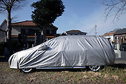 parked car with protective cover in a residential area