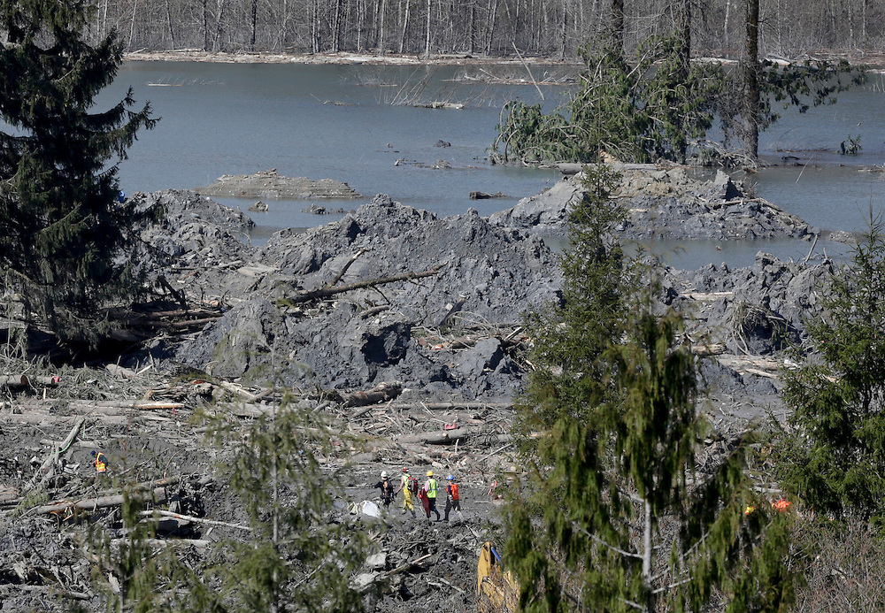 Workers walk among mud and debris as search work continues from a massive mudslide that struck Oso near Darrington, Washington April 1, 2014. Survivors of a mudslide that left dozens dead or missing in Washington state said they would like to turn the disaster site into a shrine for the victims once bulldozers clear away the mud and debris.  REUTERS/Jason Redmond (UNITED STATES)