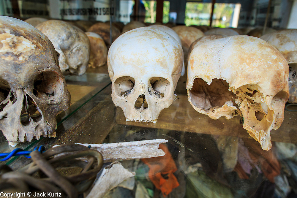 """30 JANUARY 2013 - CHEOUNG EK, CAMBODIA: Human skulls on display in the Buddhist stupa at the Choeung Ek killing fields. Choeung Ek is a former orchard and Chinese cemetery about 17 km south of Phnom Penh, Cambodia. It is the best-known of the """"Killing Fields"""", where the Khmer Rouge regime executed over one million people between 1975 and 1979. Mass graves containing 8,895 bodies were discovered at Choeung Ek after the fall of the Khmer Rouge regime. Many of the dead were former political prisoners who were kept by the Khmer Rouge in their Tuol Sleng detention center, a former high school in Phnom Penh.      PHOTO BY JACK KURTZ"""