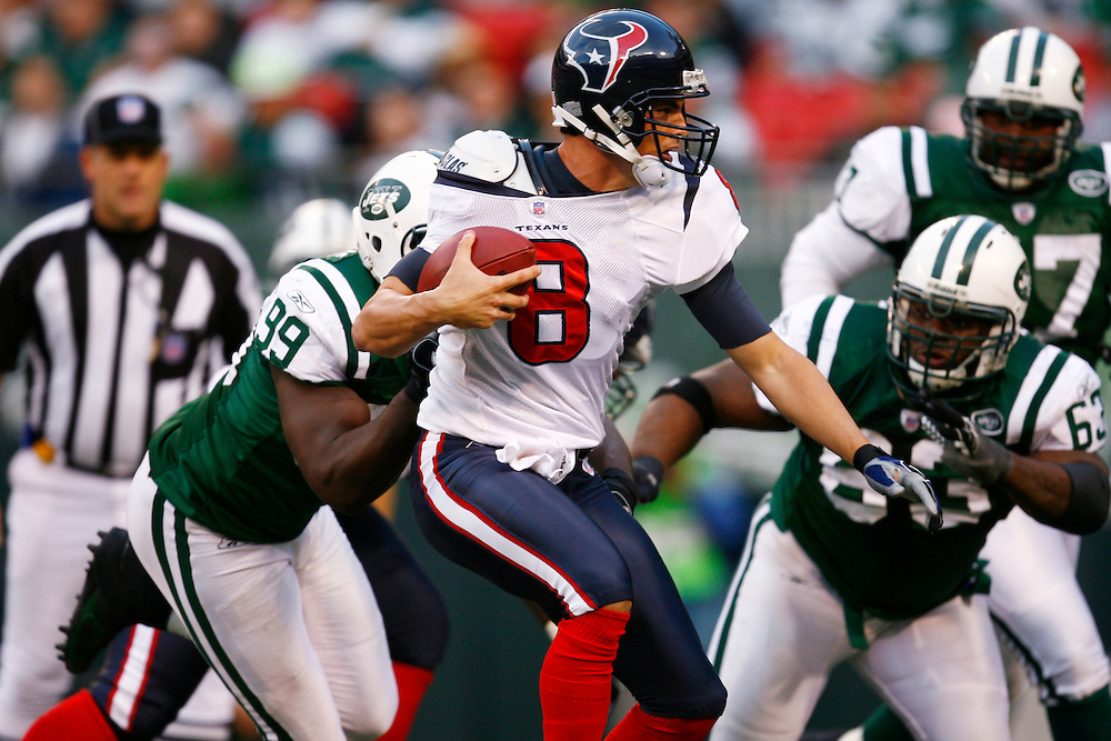 EAST RUTHERFORD, NJ - NOVEMBER 26: Quarterback David Carr #8 of the Houston Texans is pressured by Bryan Thomas #99 and Dewayne Robertson #63 of  the New York Jets at Giants Stadium on November 26, 2006 in East Rutherford, New Jersey. The Jets won the game 26-11.