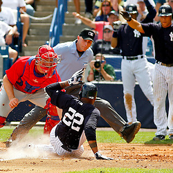 March 11, 2012; Tampa Bay, FL, USA; New York Yankees left fielder Andruw Jones (22) slides in safe past Philadelphia Phillies catcher Erik Kratz (31) scoring on a two run single by Chris Dickerson (not pictured) during the bottom of the fourth inning of a spring training game at George M. Steinbrenner Field. Mandatory Credit: Derick E. Hingle-US PRESSWIRE