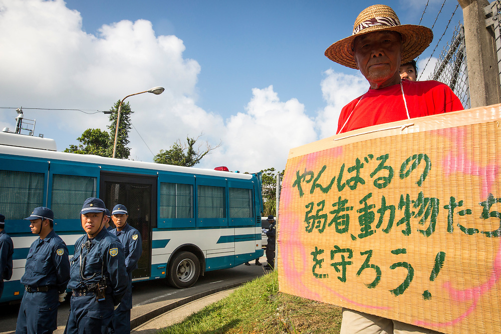 OKINAWA, JAPAN - AUGUST 19 : Anti U.S base protester with written sign to protest against the construction of helipads in front of the main gate of U.S. military's Northern Training Area in the village of Higashi, Okinawa Prefecture, on August 19, 2016. Japanese government resume construction of total six helipads in a fragile ten million year old Yanbaru forest that is home to endemic endangered species such as the Okinawan rail and Okinawa wood pecker. (Photo by Richard Atrero de Guzman/NURPhoto)