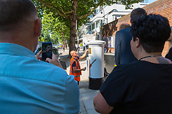 Passersby watch and take pictures on their smart phones as Tony Newlin for Royal Mail applies the vinyl decals as Royal Mail unveils a white-painted postbox outside Lords Cricket Ground with a plaque and graphics that celebrate England's ICC Cricket World Cup Victory. London, July 16 2019.
