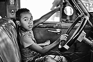 Cuban kid sitting in an old Colorful old American car in Old Havana