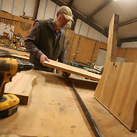 Keith checks the length of a seat before he fits it to the support to creat a new bench made from ole church pews.