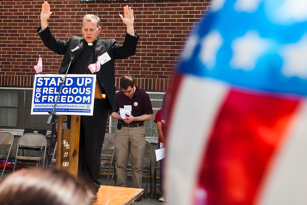 Lathan Goumas | MLive.com..Father Steve Mattson, of St. Mary Queen of Angles Catholic Church, speaks during a protest rally at St. Matthew's Roman Catholic Church in Flint, Mich. on Friday June 8, 2012. Hundreds gathered at the church to protest a healthcare policy of the Obama administration they believe forces religious institutions to pay for health services that contradict their beliefs. After a rally at the church protestors marched to the federal courthouse in downtown Flint.