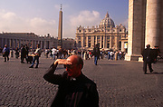 A Catholic priest shades his eyes from the sun while walking through St. Peter's Square with St. Peter's Basilica in the background, on 3rd November 1999, in Vatican City, Rome, Italy.
