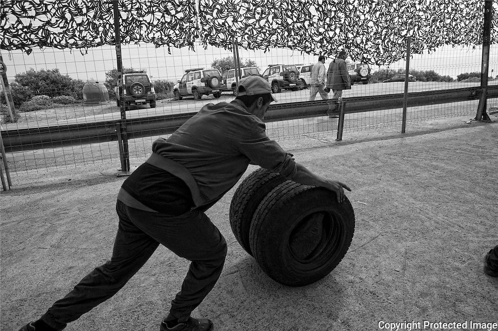 MELILLA, SPAIN - APRIL 20, 2010 : A men carrying contraband  new tires  by rotating them in order in the  border of  El Barrio Chino between Spain and Morocco on April 20 , 2010 in Melilla. Spain. Every day at the pedestrian border of El Barrio Chino hundreds of people are involved in transporting smuggled goods from Melilla a Spanish enclave on the North African coast to Morocco.For each package introduced in Morocco receive between 3 an 5 euros depending on size,with a little luck achieved make three trips a day.It is estimated that from Monday to Thursday on foot enter Melilla 8.000 porters, mostly women, to return to Morocco with huge sacks of goods from the warehouse border area of Beni Enzar in Melilla .( Photo by Jordi Cami  )