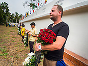 26 DECEMBER 2014 - MAE KHAO, PHUKET, THAILAND: DENNIS HOOGENKAMP, from Amsterdam, Netherlands, holds flowers at the Tsunami Memorial Wall in Mae Khao, Phuket. Hoogenkamp said he was in Phuket during the tsunami. The wall is located at the site that was used as the main morgue for people killed in the tsunami and hosts an annual memorial service. Nearly 5400 people died on Thailand's Andaman during the 2004 Indian Ocean Tsunami that was spawned by an undersea earthquake off the Indonesian coast on Dec 26, 2004. In Thailand, many of the dead were tourists from Europe. More than 250,000 people were killed throughout the region, from Thailand to Kenya. There are memorial services across the Thai Andaman coast this weekend.    PHOTO BY JACK KURTZ
