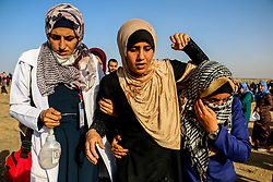 July 3, 2018 - Palestinian demonstrators are injured during a protest, joined by many Palestinian women, on the Gaza-Israeli border, east of Gaza City.  Many Palestinian women attended the demonstration, arriving in buses from across the Gaza, and some suffered injuries from tear gas and Israeli gunfire. Since the 30th of March Palestinians in Gaza have been demonstrating for the Great March of Return in support of their right to return to the lands they fled or were driven from during the 1948 war against the newly created Israel. They are also protesting against the eleven years-long blockade on the Palestinian enclave, which is causing a humanitarian crisis (Credit Image: © Ahmad Hasaballah/IMAGESLIVE via ZUMA Wire)