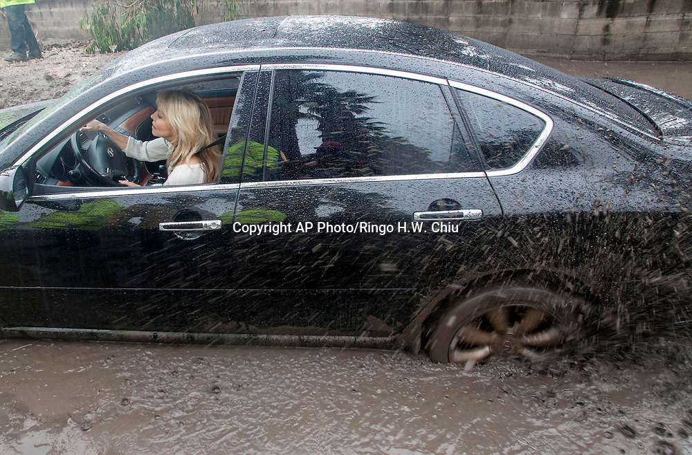 A car sits stuck in the mud brought by the rain along the hillside in Glendora, Calif. on Friday, Feb. 28, 2014. (AP Photo/Ringo H.W. Chiu)