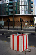 Red and white striped cuboid sits on the pavement near recently-completed housing in 2012 Olympic Stratford.