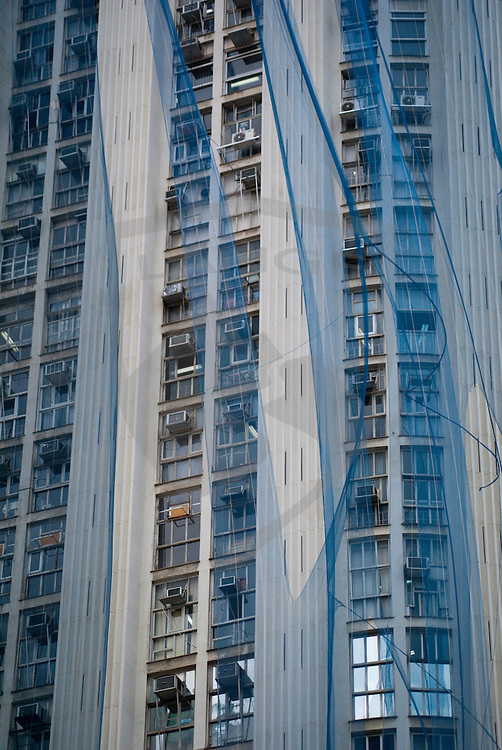 as rio de janeiro prepares for the 2016 olympics, urban renewal begins to take place.  here, a high rise building is draped in blue cloth to protect passers-by while the art deco influenced building is being painted.