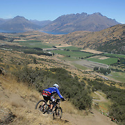 A mountain Biker in action during the NZBNZ South Island Downhill Cup mountain bike downhill series held on The Remarkables face with a stunning backdrop of the Wakatipu Basin. 150 riders took part in the two day event.  Queenstown, Otago, New Zealand. 9th January 2012. Photo Tim Clayton