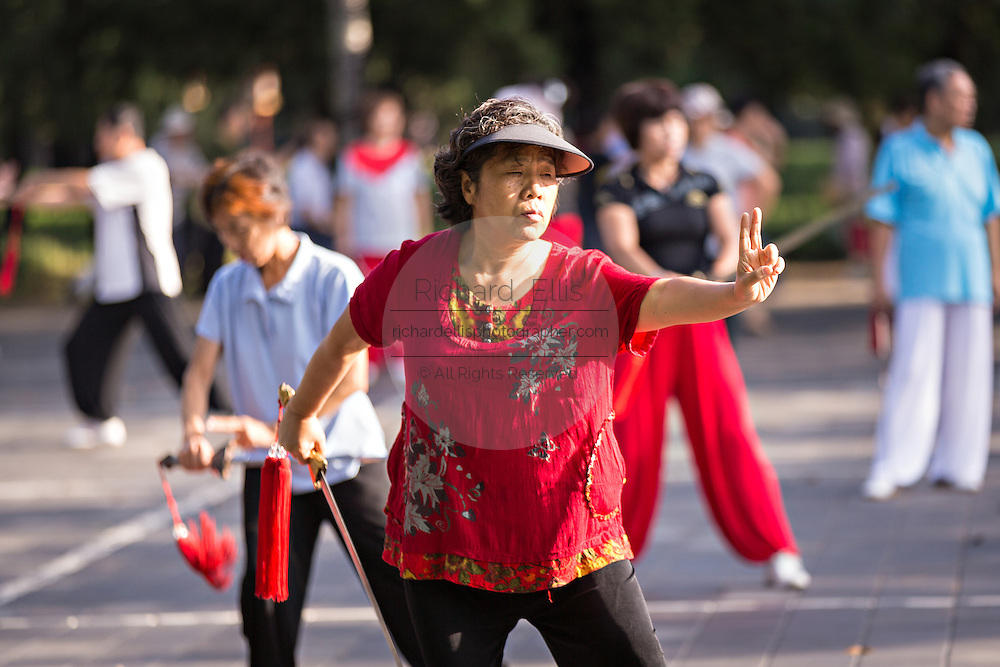 Elderly Chinese women practice sword martial arts exercise early morning at the Temple of Heaven Park during summer in Beijing, China