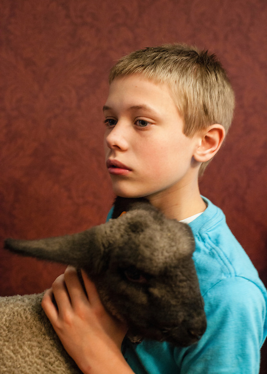 Jake Smith cares for a lamb during a community Easter event on Saturday, March 31, 2012 in Webster City, IA.