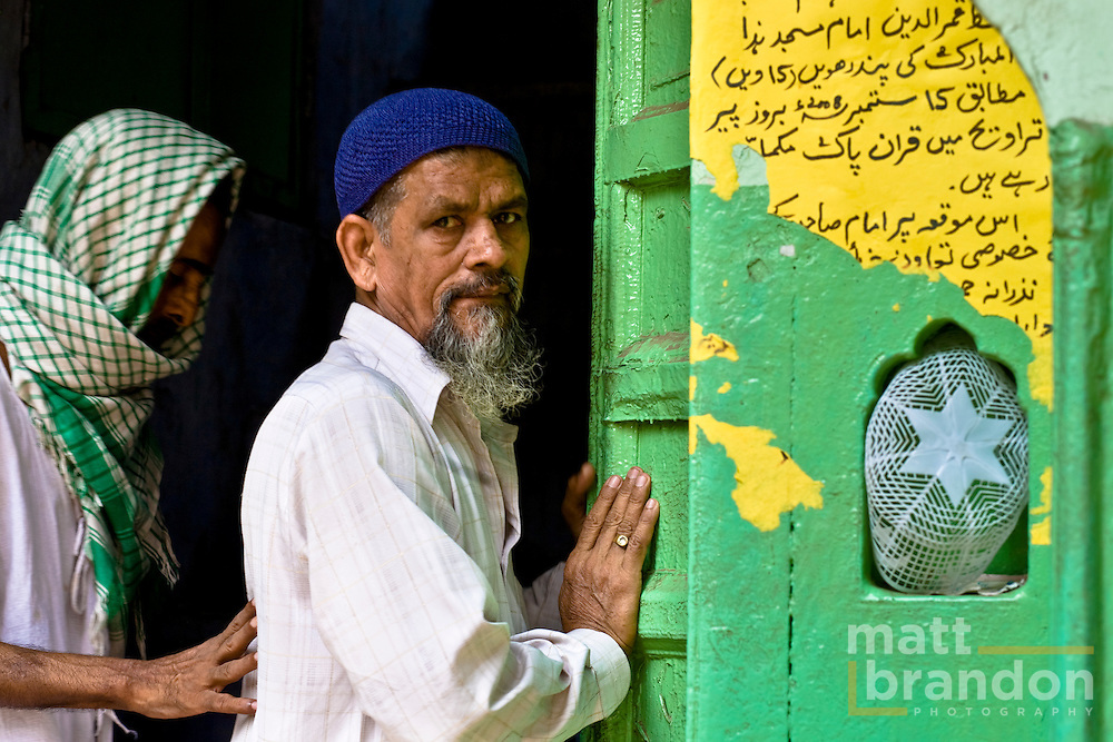 Two Muslim men enter a mosque through a green door on their way to prayers, in the back streets of old Delhi