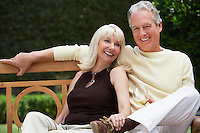 Couple Sitting on Bench in Garden