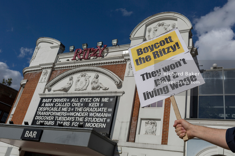 A placard is held up to the frontage of the Ritzy Cinema, part of the Picturehouse chain, in dispute with Bectu union employees for a living London wage, on 3rd July 2017, in Brixton, London, England. The Picturehouse chain is owned by Cineworld which has 2,000 cinema screens in nine countries. The London Living Wage is set at £9.75 per hour (the national rate is £8.45).