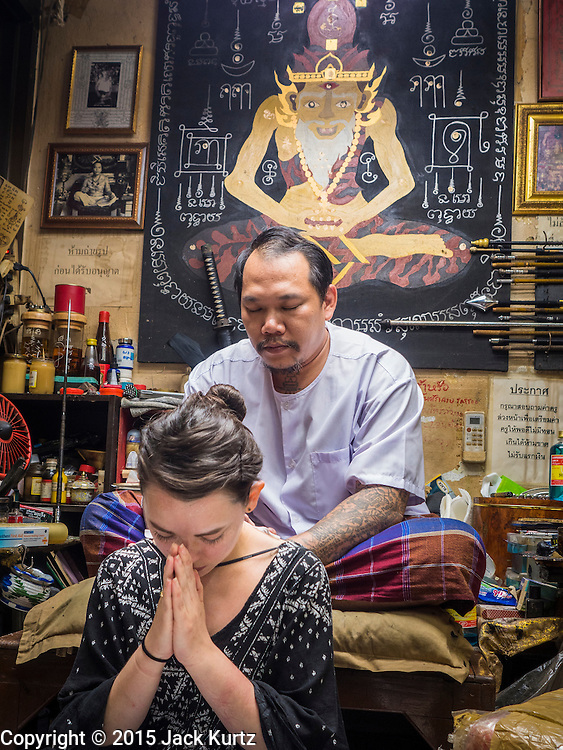"""25 MAY 2015 - BANGKOK, THAILAND: VANESSA, an American visitor to Thailand,  gets a Sak Yant tattoo from AJARN NENG ONNUT. Sak Yant (Thai for """"tattoos of mystical drawings"""" sak=tattoo, yantra=mystical drawing) tattoos are popular throughout Thailand, Cambodia, Laos and Myanmar. The tattoos are believed to impart magical powers to the people who have them. People get the tattoos to address specific needs. For example, a business person would get a tattoo to make his business successful, and a soldier would get a tattoo to help him in battle. The tattoos are blessed by monks or people who have magical powers. Ajarn Neng, a revered tattoo master in Bangkok, uses stainless steel needles to tattoo, other tattoo masters use bamboo needles. The tattoos are growing in popularity with tourists, but Thai religious leaders try to discourage tattoo masters from giving tourists tattoos for ornamental reasons.       PHOTO BY JACK KURTZ"""