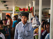 30 OCTOBER 2015 - YANGON, MYANMAR:  A watermelon vendor carries her inventory on her head on the Dala ferry. The ferry to Dala runs continuously through the day between Yangon and Dala. Yangon, Myanmar (Rangoon, Burma). Yangon, with a population of over five million, continues to be the country's largest city and the most important commercial center.          PHOTO BY JACK KURTZ