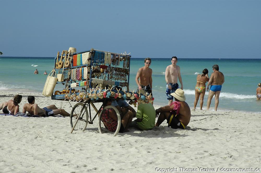 Strandszene: Touristen am Strand der kubanischen  Ferien-Metropole Varadero passieren den mobilen Stand eines Souvenir-Verk?ufers