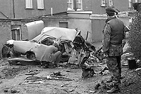 Remains of the booby-trapped car at the rear of his home in which Edward Clayton, 27 years, breadserver, Armagh, N Ireland, died on 6th March 1975. The explosion was believed to have been carried out by the Provisional IRA but almost certainly they got the wrong man as Clayton had no security force or para-military connections. The victim's brother would almost certainly have died in the explosion had he not gone back at the last minute to get a raincoat. Soldiers stand guard as forensics officer investigates. 197503060205.<br /> <br /> Copyright Image from Victor Patterson, 54 Dorchester Park, Belfast, UK, BT9 6RJ<br /> <br /> t1: +44 28 9066 1296 (from Rep of Ireland 048 9066 1296)<br /> t2: +44 28 9002 2446 (from Rep of Ireland 048 9002 2446)<br /> m: +44 7802 353836<br /> <br /> victorpattersonbelfast@gmail.com<br /> victorpatterson@me.com<br /> <br /> www.victorpatterson.com<br /> <br /> Please see my Terms and Conditions of Use at https://www.victorpatterson.com/page2<br /> It is IMPORTANT that you familiarise yourself with them.<br /> <br /> Images used on the Internet incur an additional cost and must be visibly watermarked i.e. © Victor Patterson within the body of the image and copyright metadata must not be deleted. Images used on the Internet have a size restriction of 4kbs and are chargeable at rates available at victorpatterson.com.<br /> <br /> This image is available only for the use of the download recipient i.e. television station, newspaper, magazine, book publisher, etc, and must not be passed on to any third party. It is also downloaded on condition that each and every usage is notified within 7 days to victorpatterson@me.com<br /> <br /> The right of Victor Patterson (or the named photographer) to be identified as the author is asserted in accordance with The Copyright Designs And Patents Act (1988). All moral rights are asserted.