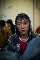 """Habibullah Qasimi, a 17-year-old migrant from Afghanistan, waits for a ferry to the Greek mainland on a rainy night at the port in Mytilene, on the Greek island of Lesbos. He is one of the more than 500,000 migrants and refugees who had landed in the Greek islands from Turkey in 2015.  He gave his email address to the photographer and underneath it wrote """"We are tired of my life."""""""