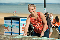 A mile of buskers on Portobello Prom this afternoon in the nonth annual Big Beach Busk. The day starts with the man who first came up with the idea for the busk, ?Paul Lambie and his team of local helpers chalking out the circular 'pittches' all along the Prom. And then the buskers arrive - all ages, all styles of music, from solo performers to big bands. The place is heaving! Megan Davey helping to get the Prom ready for the buskers.<br /> <br /> <br /> © Jon Davey/ EEm