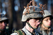 Apr, 10, 2011, Camp Edwards, Massachusetts - Cadet Jon Broderick uses leaves to help add camoflauge to his helmet. Photo by ©Lathan Goumas.