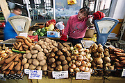 An apple-cheeked girl selling root vegetables waits for customers at Ulaanbaatar, Mongolia's central retail market. Hungry Planet: What the World Eats (p. 230). This image is featured alongside the Batsuuri family images in Hungry Planet: What the World Eats.