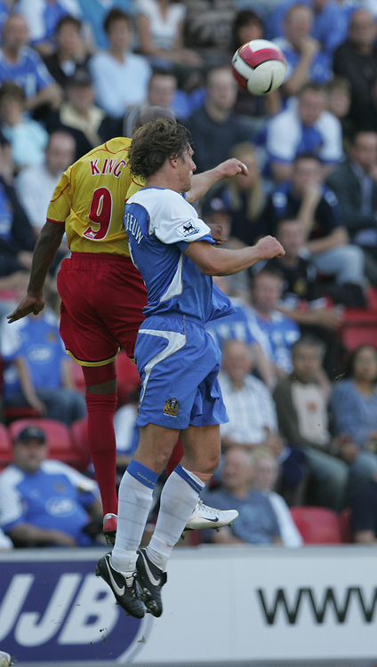 Photo: Andi Thompson.<br />Wigan Athletic v Watford. The Barclays Premiership. 23/09/2006.<br />Wigan's Arjan De Zeeuw (R) and Watford's Marlon King (L) Challenge for the ball